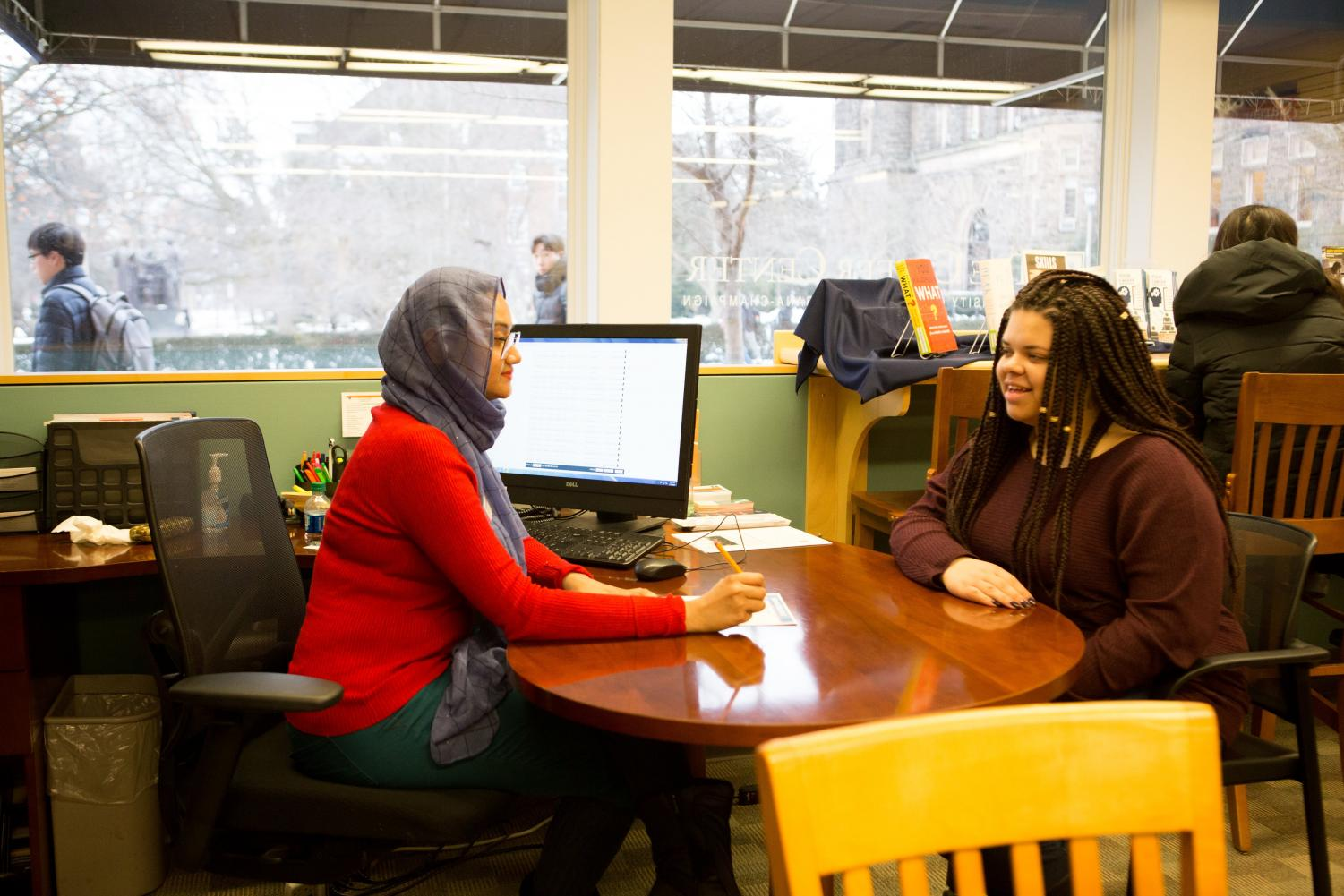 Shoptorshi Rahman (left) and Alexis Young (right) walk through a sample resume at the Career Center on Thursday.
