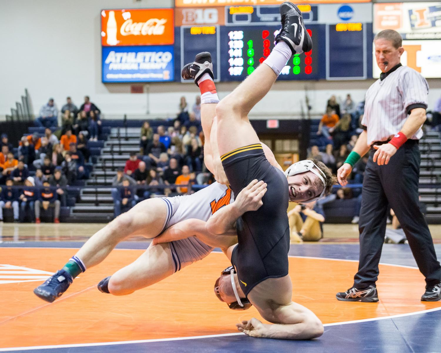 Illinois' Eric Barone wrestles with Iowa's Kaleb Young in the 157-pound match at Huff Hall on Friday. The Illini lost 31-8.