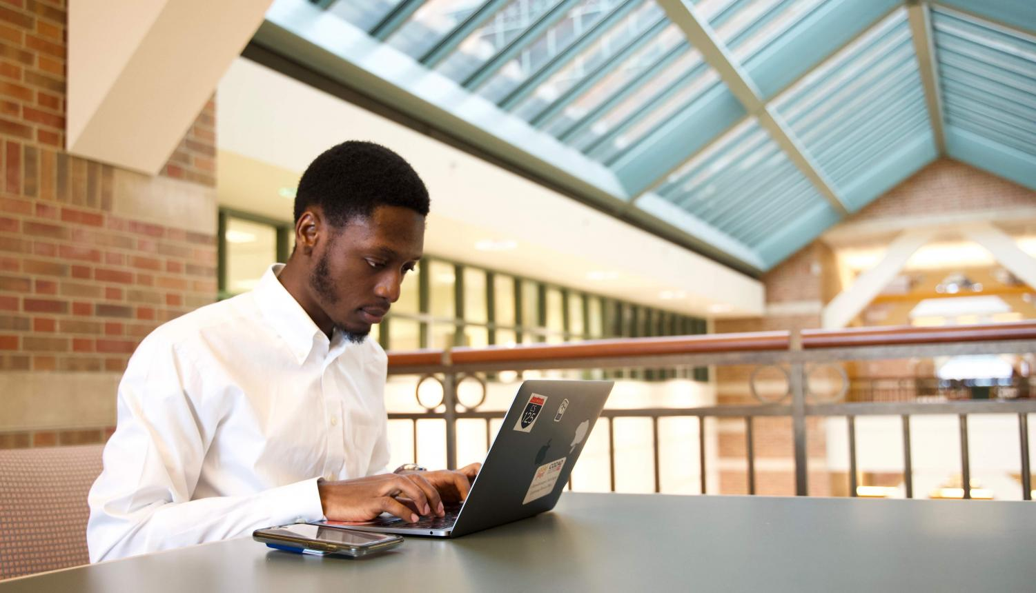 "Oluwabusayo Adebayo, sophomore in ACES, works on his computer Tuesday. Adebayo developed the app ""Subawu"" to connect STEM students."