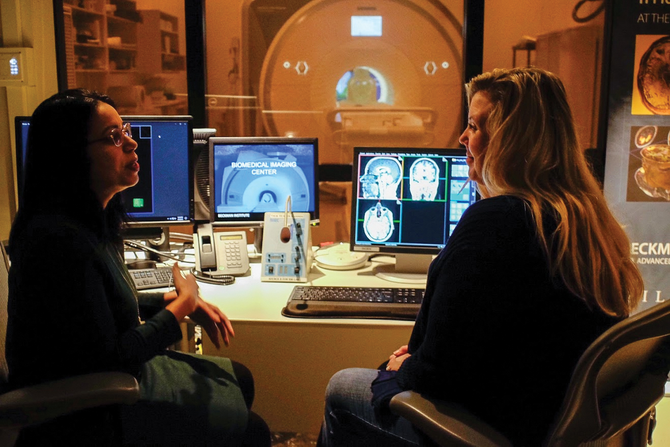 Fatima Husain (left) and Holly Tracy (right), MRI technologist, discuss brain-imaging tools in the Biomedical Imaging Center at the Beckman Institute for Advanced Science and Technology on Thursday.