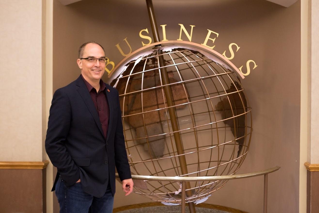 Dr. Robert Brunner poses in front of the globe in Wohlers Hall on Thursday. He is the Gies College of Business' new associate dean for innovation and chief disruption officer.