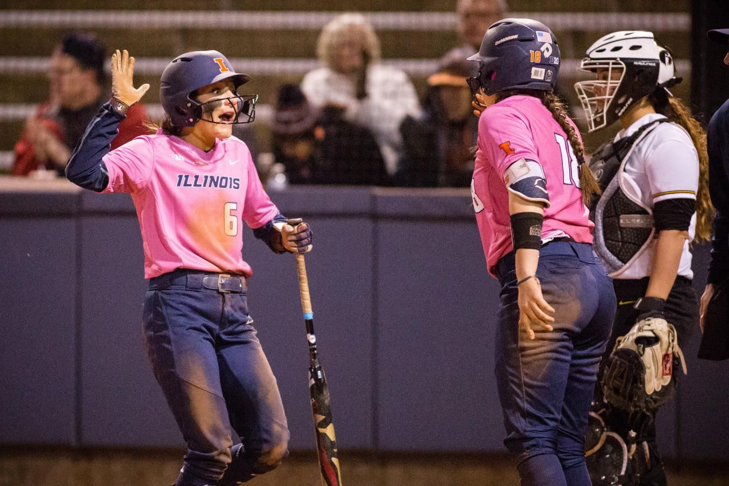Illinois outfielder Kiana Sherlund (left) celebrates with catcher Bella Loya (right) after scoring a run in the bottom of the seventh to make the score 5-5 against Iowa at Eichelberger Field on April 21. The Illini won 6-5. Sherlund and Loya are excited to start the new season and build on their skills.