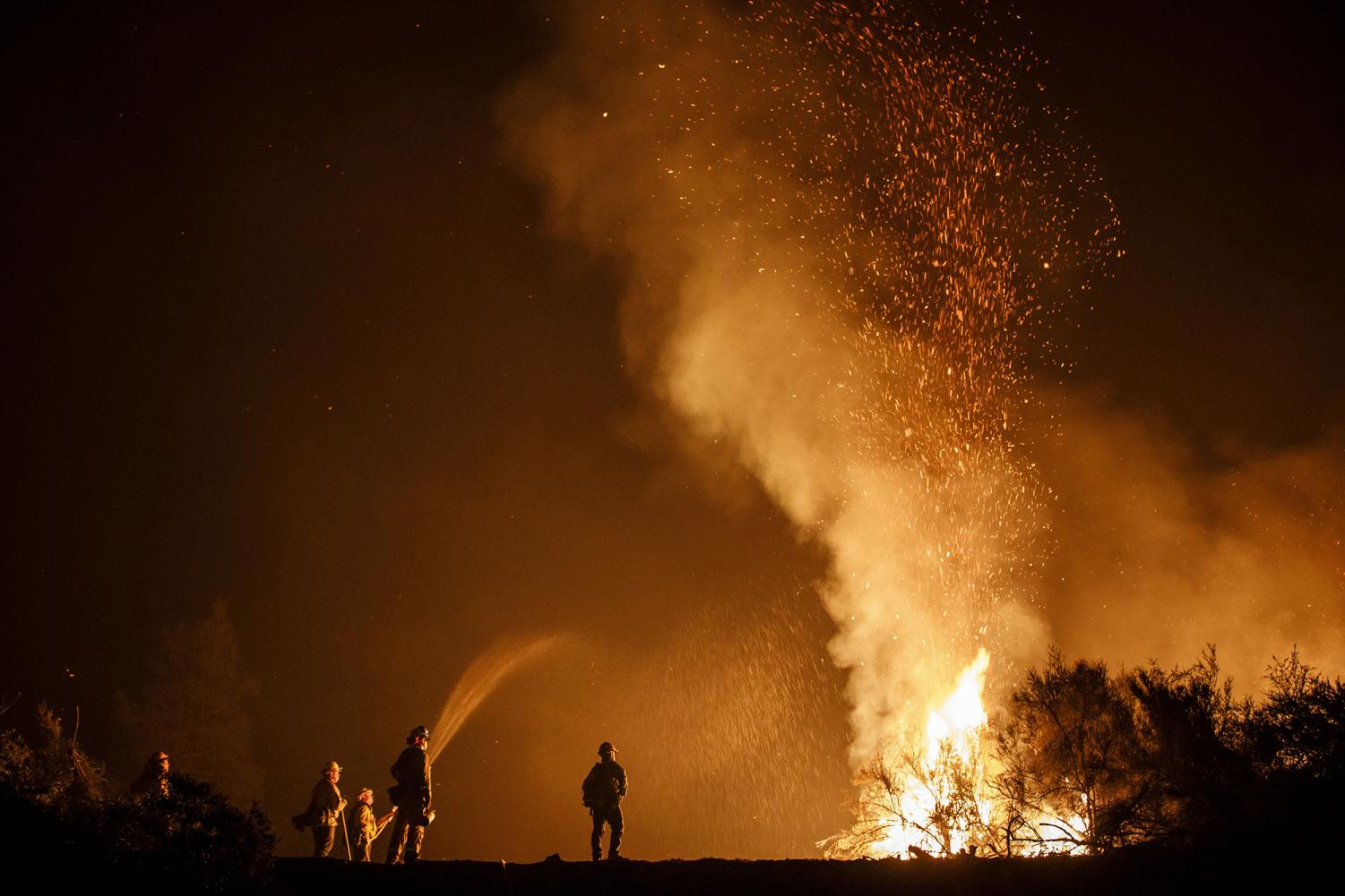 Firefighters monitor a burn operation on top of a ridge near the town of Ladoga, Calif., on August 7, 2018.
