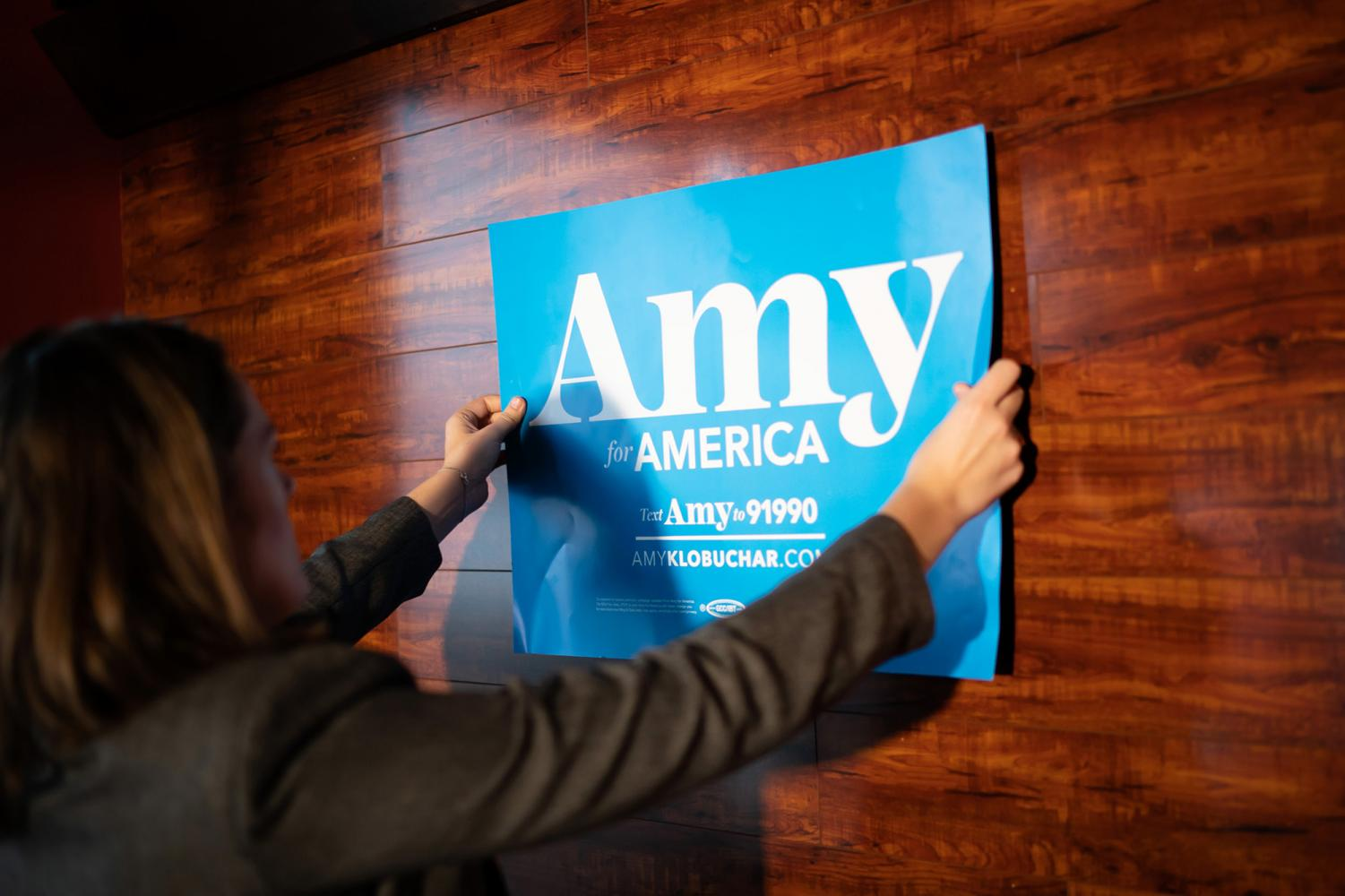 Staffer Greta Oanes tapes a Klobuchar sign on the wall, where Amy Klobuchar would speak to the Marion County Democrats, at a soup luncheon on Sunday, February 17, 2019 at Peace Tree Brewing Company in Knoxville, Iowa.
