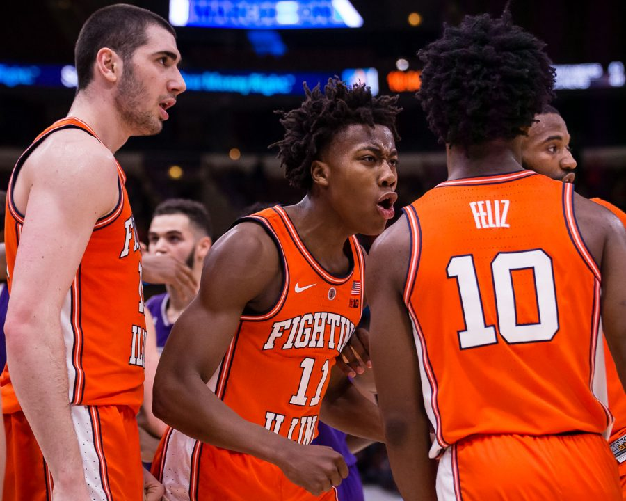 Illinois guard Ayo Dosunmu (center) celebrates with guard Andres Feliz (right) during the game against Northwestern in the first round of the Big Ten Tournament at the United Center on Wednesday.
