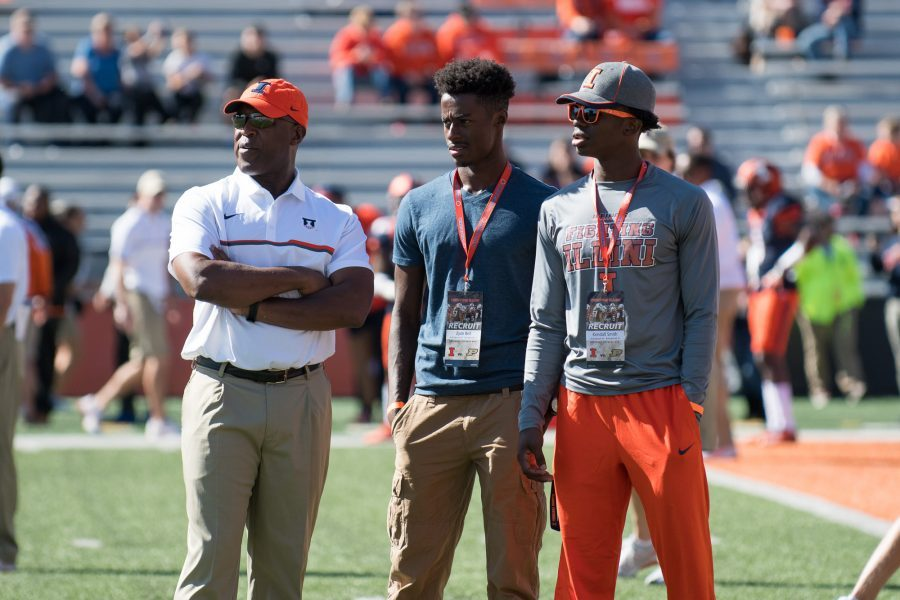 Head coach Lovie Smith talks with potential basketball recruits Zyon Bel and Kendall Smith before the game against Purdue at Memorial Stadium on Oct. 8. Smith and Julian Pearl swap positions of players in spring practices.
