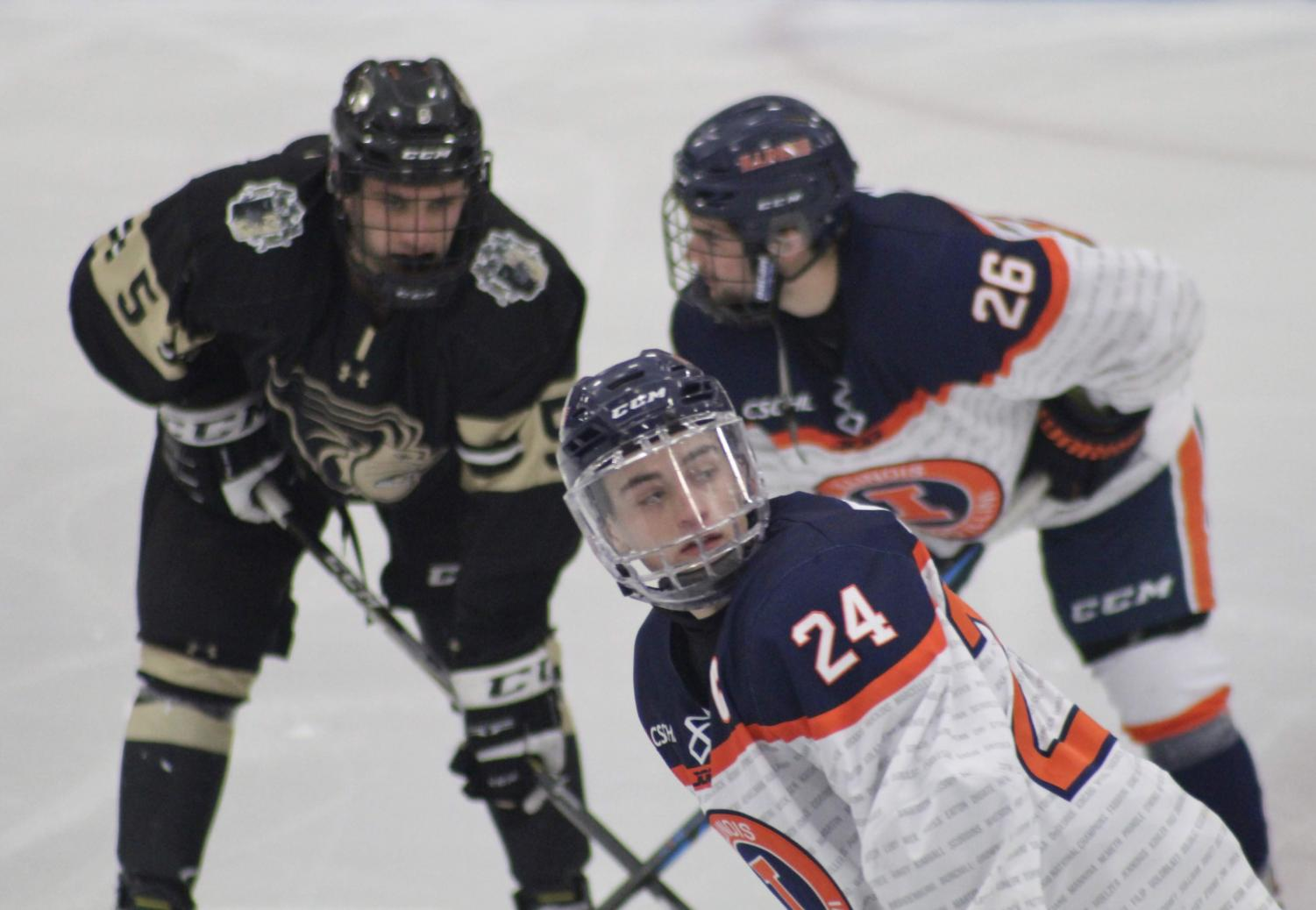 Illinois forwards Bobby Ernsting (front) and Thomas Kolaz (back) face off with a Lindenwood player during the Illinois vs. Lindenwood game at the Ice Arena on Jan. 18. Illinois lost 2-1.