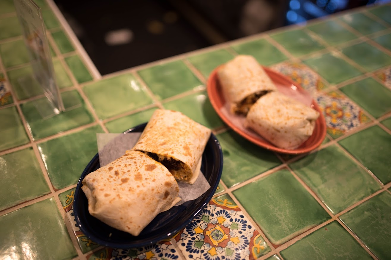 Burritos made by the chefs at Maize Mexican Grill are placed on the counter inside the restaurant on Sunday.