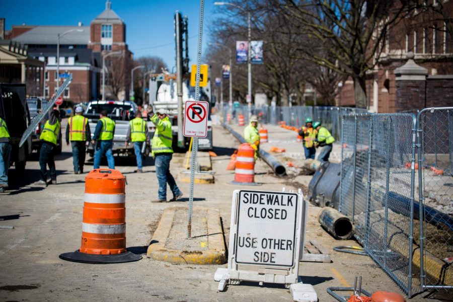 Construction workers on Wright Street on Tuesday. The east side of the street between Daniel and Armory streets is closed to pedestrians.