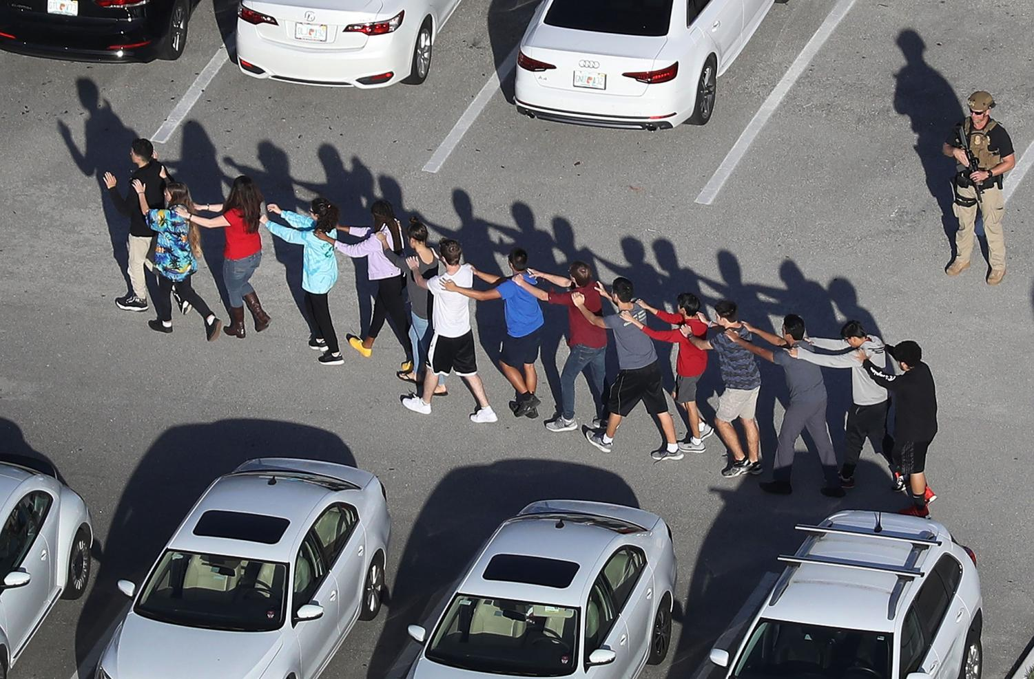 People are brought out of the Marjory Stoneman Douglas High School after a shooting at the school that reportedly killed and injured multiple people on February 14, 2018 in Parkland, Florida. Numerous law enforcement officials continue to investigate the scene.