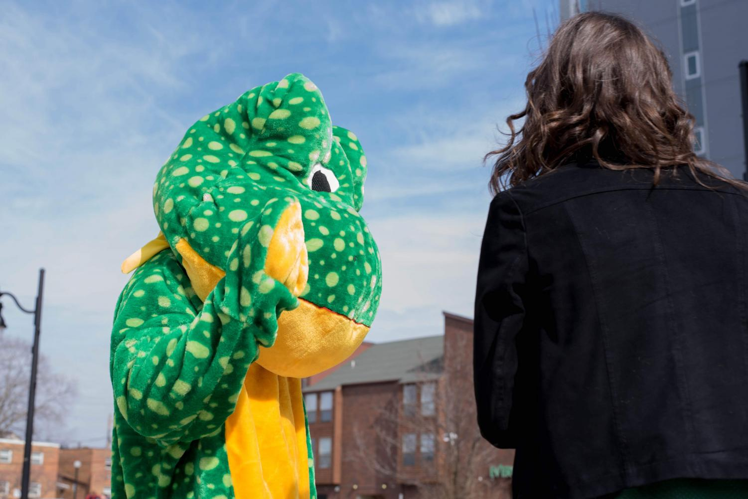 A+man+dressed+in+a+frog+costume+high-fives+an+individual+in+Champaign+during+Unofficial+on+Friday.