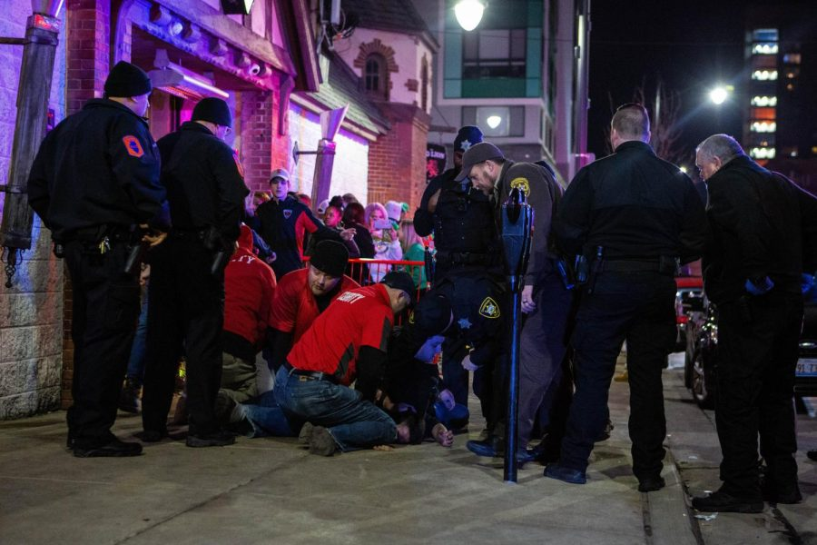Police and security personnel care for a man with problems breathing during Unofficial on Friday.