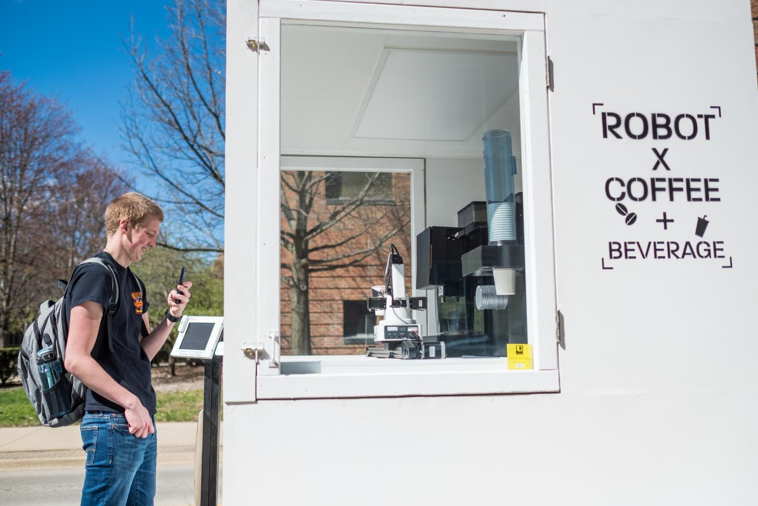 Cody Bainbridge, sophomore in Engineering, buys coffee from the Robot x Coffee Machine outside of Grainger on Apr. 14. The robot serves between 100 to 200 cups a day.