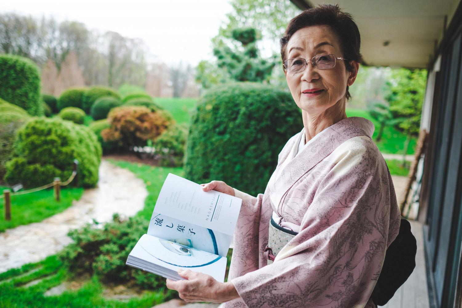 "Kimiko Gunji shows off a page in her book, ""The Art of Wagashi"" at the Japan House on Thursday. The book attempts to make recipes accessible to inexperienced audiences."