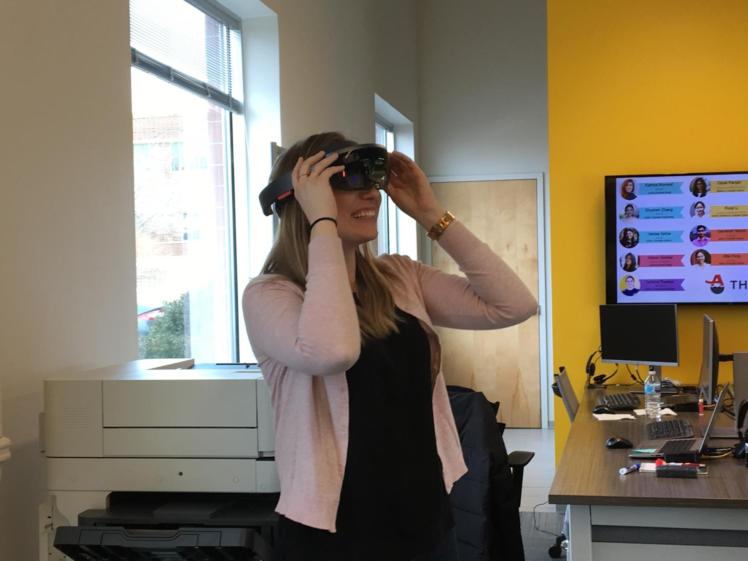 Sarah Woody tries on glasses for a recent augmented reality project at AARP's technology lab, The Tech Nest, in Research Park. AARP is a nonprofit organization that strives to benefit those who are aging with innovative solutions.