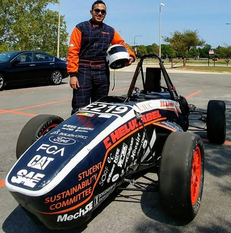 Shreyas Dmello stands in front of one of the formula electric cars he helped build. The Illini Formula Electric team has allowed Dmello to apply what he learned in the classroom.