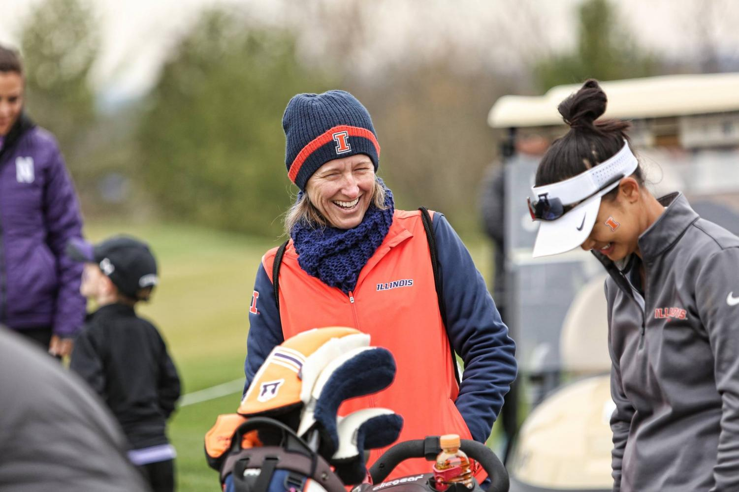 Women's golf head coach Renee Slone laughs alongside an Illini golfer. Slone was awarded Big Ten Coach of the Year.