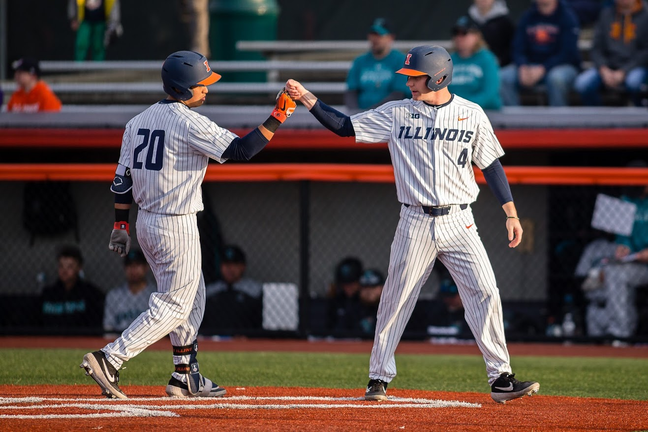 Illinois second baseman Branden Comia (left) celebrates with shortstop Ben Troike (right) after hitting a two-run home run during the game against Coastal Carolina at Illinois Field on Tuesday. The Illini won 4-2.