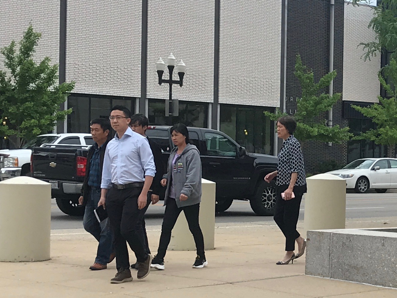 Leaving the courthouse Wednesday, members of Yingying Zhang's family walk behind Zhang's fiancé, Xio Linhou who she planned to marry in October 2017. Opening statements began Wednesday morning following the testimonies of nine witnesses brought in by the government.