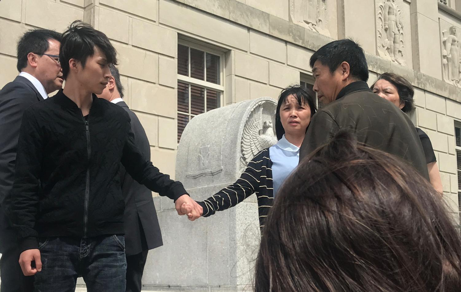 Xinyang Zhang, Yingying's brother (right), leads their mother Lifeng Ye (center) after the family addresses the public. Ronggao Zhang, Yingying and Xinyang's father (left), made the statement. Brendt Christensen was found guilty by the jury on June 24.