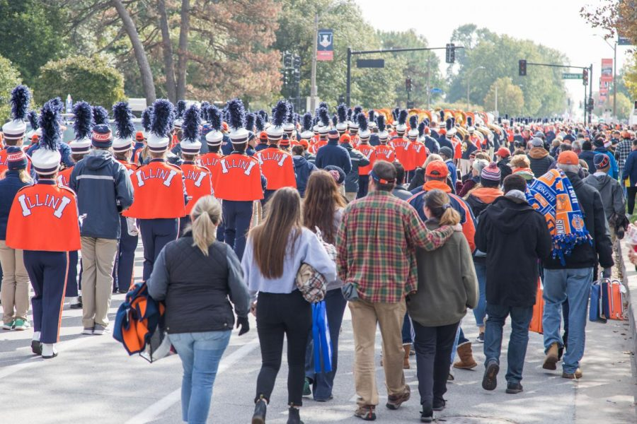 Pedestrians walk toward Memorial Stadium alongside the Marching Illini on Oct. 18. Synonymous with school spirit itself, the Marching Illini accompany many scenes of Illini pride like football games and Quad Day.