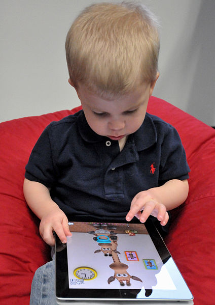 A child plays a video game on a tablet. Columnist Ellen urges parents to allow their children to be bored and, thus, cultivate their imagination rather than drown them in technology.
