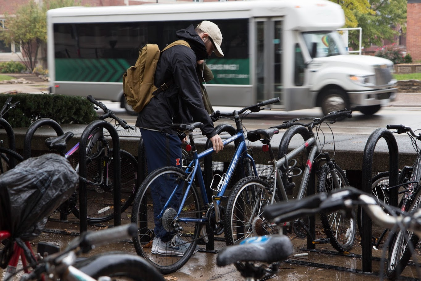 A student unlocks his bike next to Wright Street on Oct. 26. Columnist Andrew argues the existing dichotomy in the fat shaming debate is a fallacy and proposes a third cause: American culture. Bicycling is a great way to offset the sedentary lifestyle.
