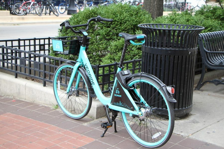 A Veoride bicycle is parked on a sidewalk in Champaign. The rentable bicycles lie all around campus and can promote hazardous situations if improperly parked.