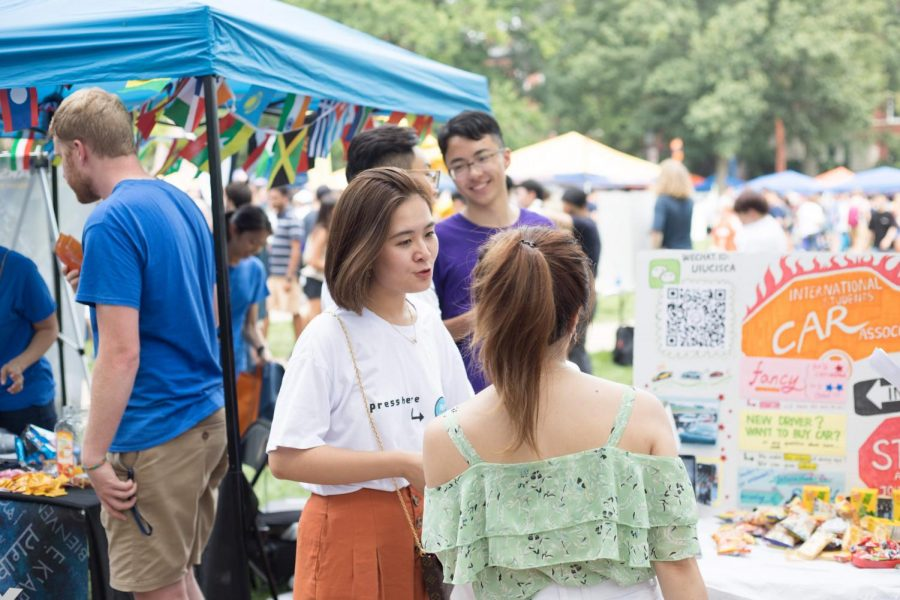 A student speaks to a representative of the International Student Car Association during Quad Day on Aug. 26. Even though the massive crowds may be terrifying -- especially to a new student -- seeking out opportunities on your own has many benefits.