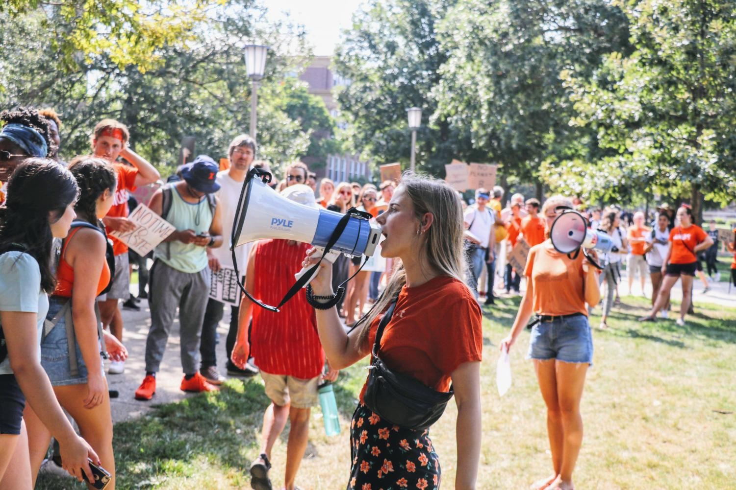 A student rallies participants of the climate change march on Sept. 20. Students and members of the local community gathered to join in protesting the government's lack of influence in combating climate change.