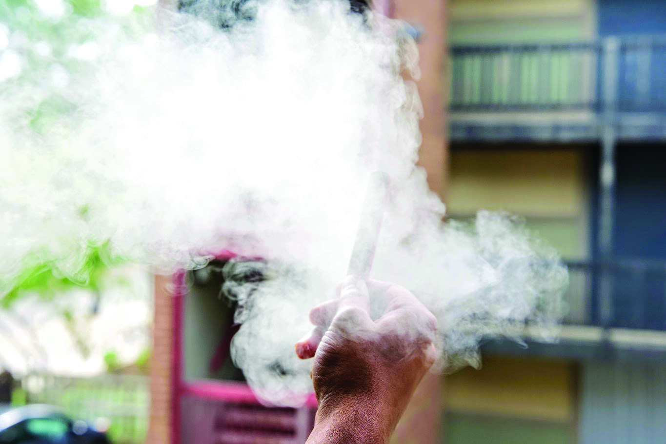 A student vapes in an apartment complex near the North Quad on Saturday. As of Aug. 26, the University is a smoke-free and tobacco-free campus.