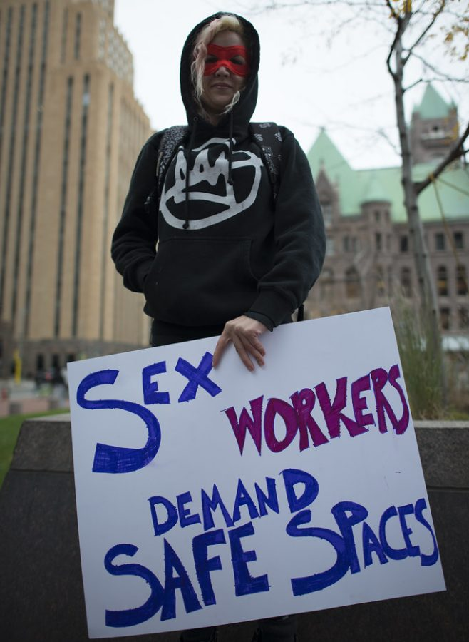 An unidentified sex worker holds a sign at the Minneapolis  protest against the raid and arrests at Backpage on Oct. 6. Columnist Andrew points out  a well-known bill will eliminate platforms, like Backpage, that sex workers use to safely find clients.