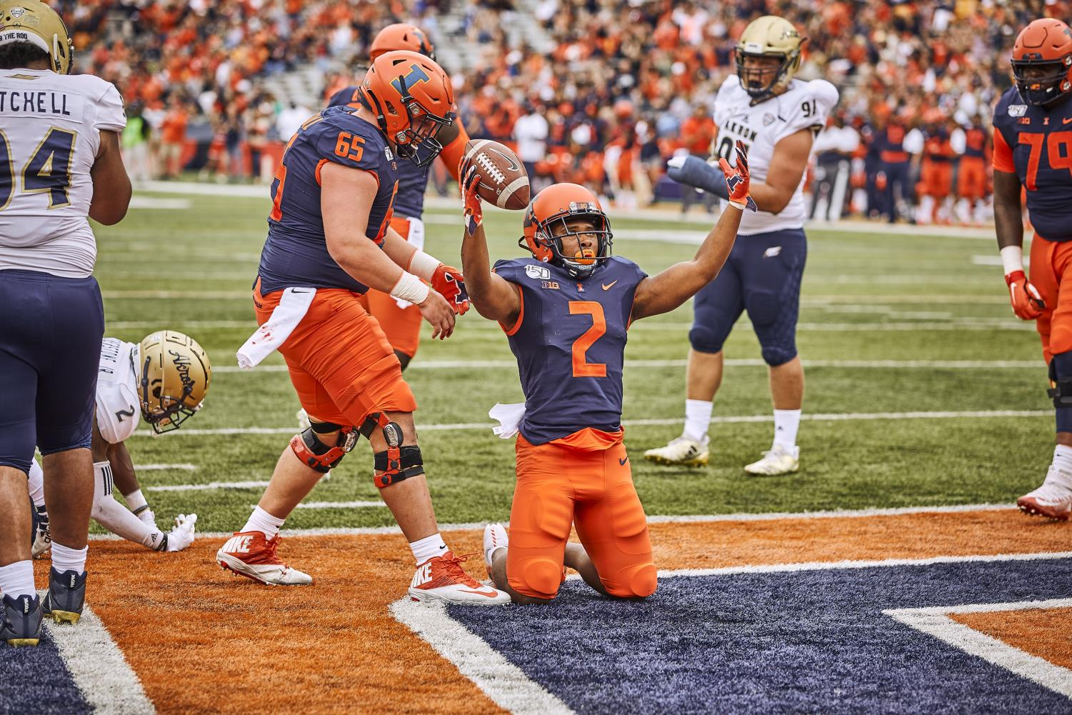 Senior Reggie Corbin celebrates in the end zone after scoringe a touchdown during the Illini's game against the Akron Zips. Corbin feels pressure in his publicized position, and writing provides an escape.