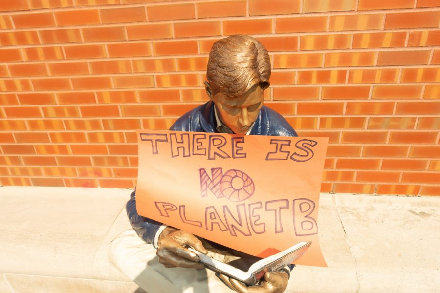 Grainger Bob holding a Climate March sign outside Grainger Library on Friday.