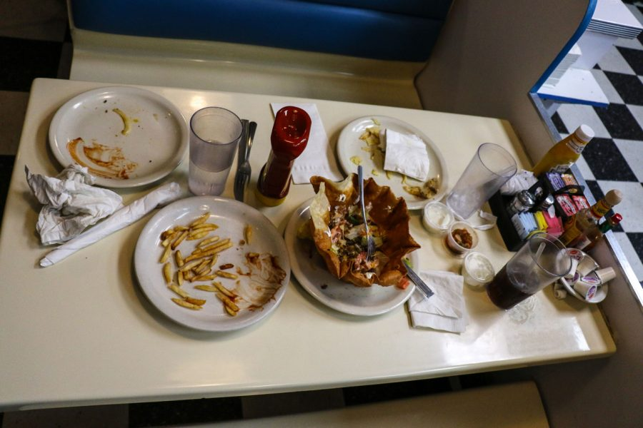 A table of plates left by customers wait to be cleaned off the table.