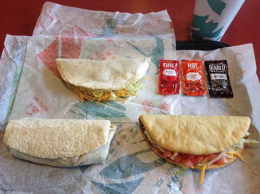 Several Taco Bell menu items. Clockwise from lower right: chalupa supreme, combo burrito, double decker taco.