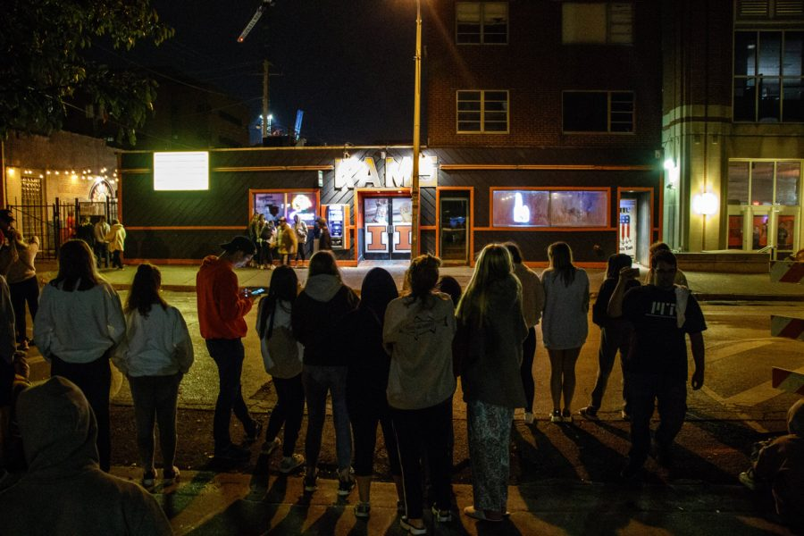 People stand in front of KAM's as its final hour comes near Sunday night.