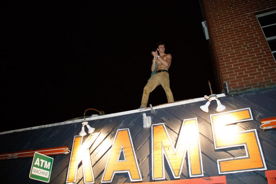 A KAM's patron hypes up the crowd while standing on top of the bar.