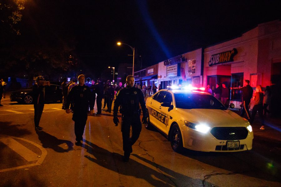 Champaign police approach the growing crowd outside KAM's.