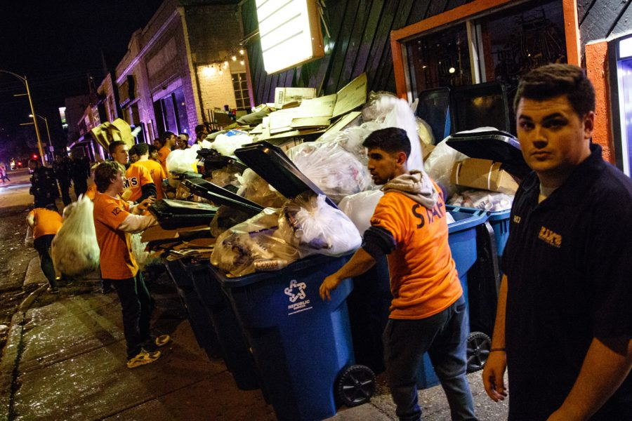 Employees of KAM's take out trash bags after a busy final night.
