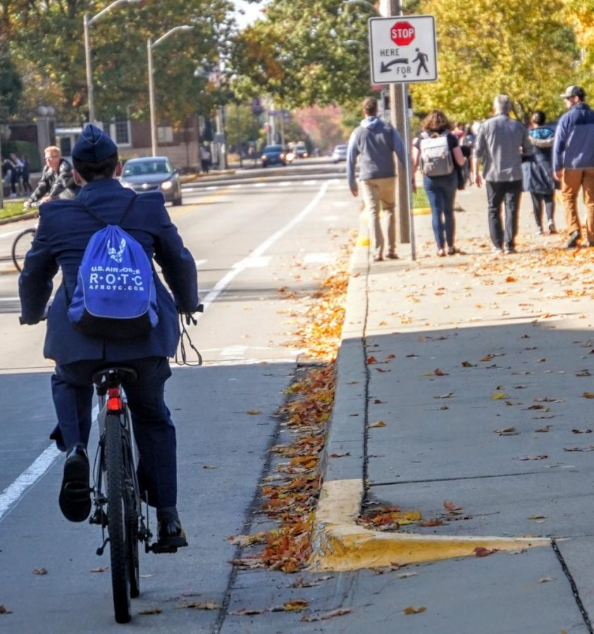 A cyclist passes by a group of people on West Gregory drive on Sunday. The University of Illinois was recently promoted to silver-level Bicycle-Friendly University by the League of American Bicyclists.