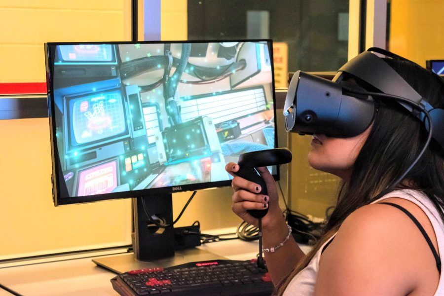 Nancy Torres, a junior in Business, explores to capabilities of the VR headset as she plays one of the interactive games on the computer in the Virtual Reality Lab at the Armory on Thursday. The workshops provide an opportunity for students, faculty and community members to learn about VR and use the technology.