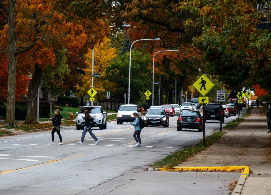Students cross Lincoln and Indiana avenues on Tuesday. The City of Urbana is working to create more regulations for pedestrians to reduce accidents and improve safety for residents crossing Lincoln Avenue.