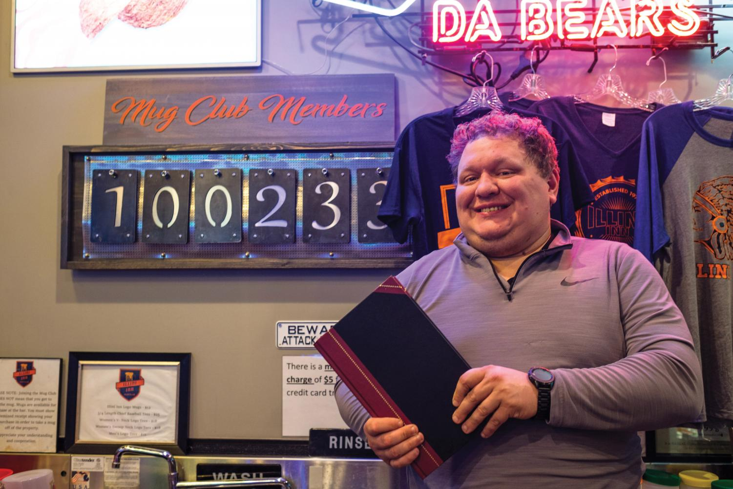 Josh Pearson, manager of Illini Inn, poses in front of the mug club sign on Tuesday