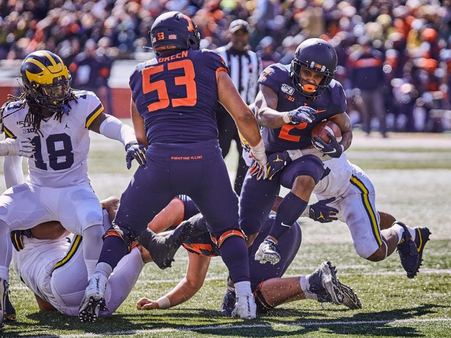 Illinois+tight+end+Justice+Williams+jumps+through+Michigan+defenders+during+the+game+against+the+Wolverines.+The+Illni+lost+42-25.