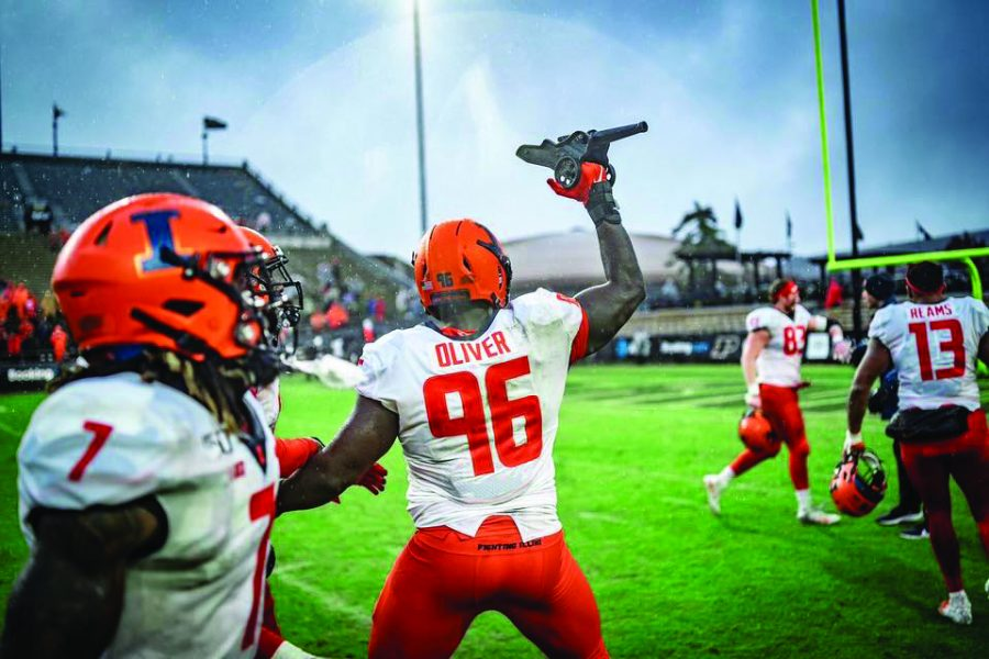 Defensive lineman Tymir Oliver (96) celebrates with the cannon after beating Purdue 24-6. The Illinois defense kept Purdue at 6 points Saturday.