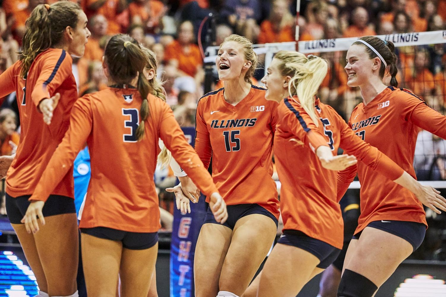 Megan Cooney (15) celebrates with the Illini Volleyball team at Huff Hall at the Illini's game vs. Iowa on Sep 28. Although her position change has posed challenges, Cooney is using her past experiences and team practices to improve.