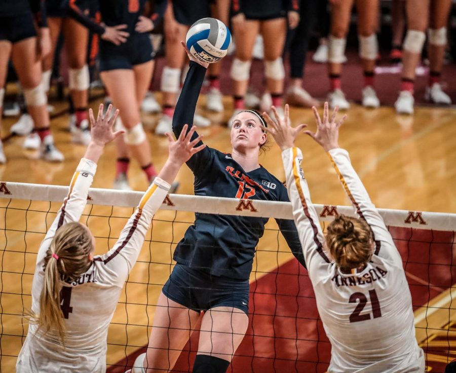 Senior Ashley Fleming sets the ball over two Minnesota defenders in Maturi Pavilion Saturday. The Illini lost to the Gophers 3-1.