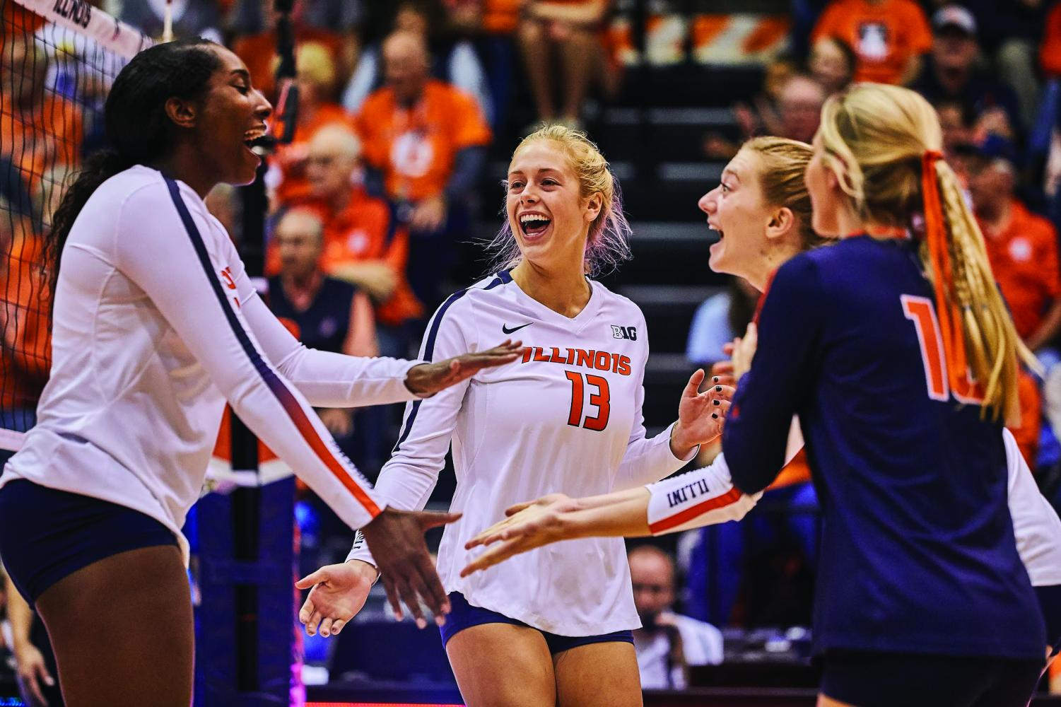 Mica Allison (13) celebrates with the Illini volleyball team after scoring a point at Huff Hall against Indiana on Saturday. Allison, who transferred from Auburn University this season, brings a variety of position experience to the table.