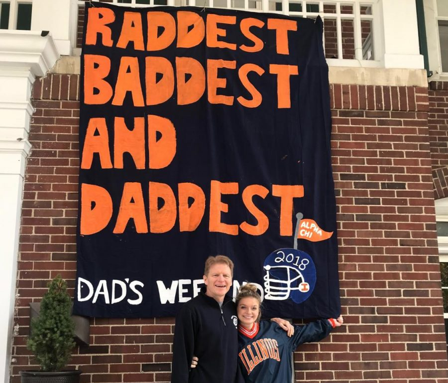 Bella Keys and her father stand in front of a sign at the Alpha Chi Omega house. Bella enjoys bonding with both her parents each Dads Weekend.
